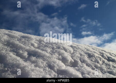 mountain slope covered with white fluffy snow against the blue sky low angle view - Stock Photo