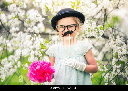 Funny girl in hat, glasses and gloves and with fake mustache playing in spring garden. - Stock Photo