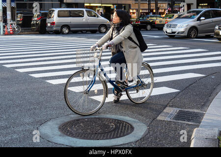 Japanese female cyclist commuting by bicycle in Ginza, Tokyo. - Stock Photo
