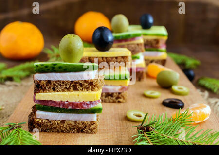 Mini sandwiches (canape) with fresh cucumbers, ham, cheese, olives, salami, black bread on a cutting board. Close - Stock Photo