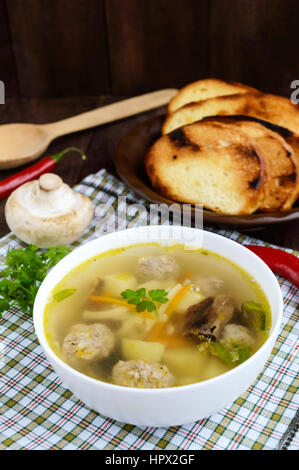 Light soup with dried mushrooms, meatballs and maccheroni in a white bowl - Stock Photo