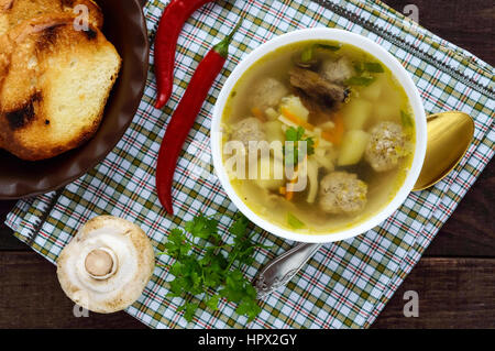 Light soup with dried mushrooms, meatballs and maccheroni in a white bowl. The top view - Stock Photo