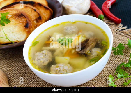 Light soup with dried mushrooms, meatballs and maccheroni in a white bowl. Close-up. - Stock Photo