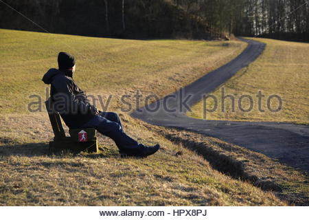 A middle-aged man in cap and winter jacket sits on a bench looking towards a path bathed in evening sunlight - Stock Photo