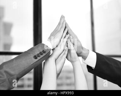 businesspeople putting hands together to form a pyramid in a display of team spirit and determination, black and - Stock Photo