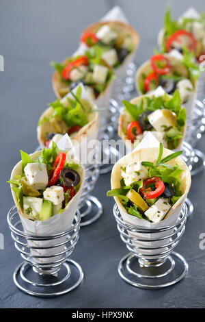 Mini tortillas stuffed with Greek farmers salad with feta cheese and olives, served in wire egg cups - Stock Photo