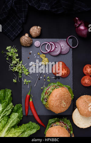 Closeup of homemade burgers with fresh vegetables on slate board. Healthy food still life, top view. - Stock Photo