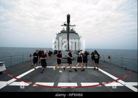 Sailors from the first class petty officer mess and the Chiefu2019s mess run laps around the ship during physical - Stock Photo