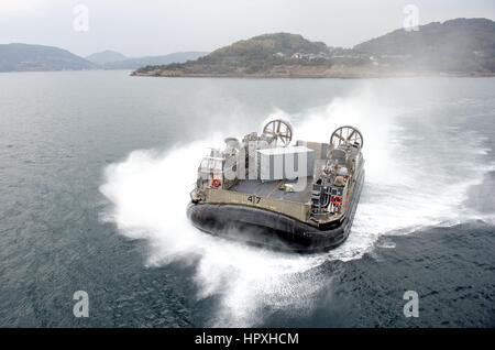 A landing craft air cushion (LCAC) approaches the stern gate of the amphibious assault ship USS Bonhomme Richard - Stock Photo