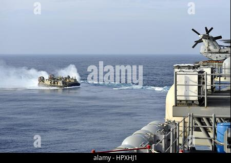 A landing craft air cushion approaches the stern of the amphibious assault ship USS Bonhomme Richard, East China - Stock Photo
