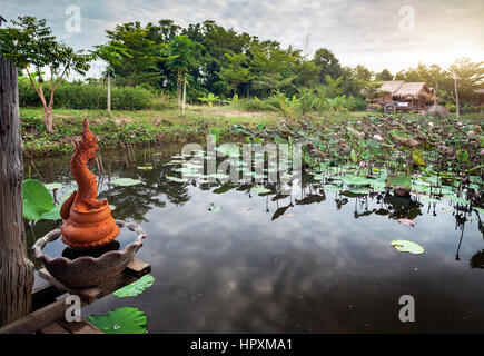 Beautiful pond with lotus and Dragon statues in Sukhothai resort, Thailand - Stock Photo