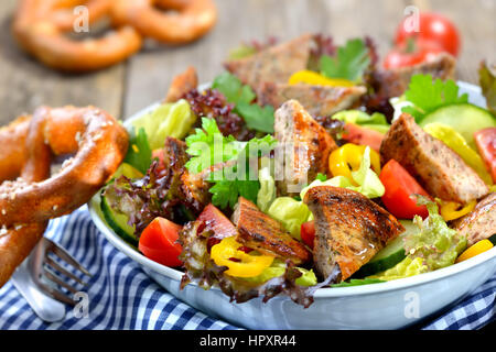 Bavarian salad: Pieces of fried sausage with pig spleen served on a colorful mixed salad - Stock Photo
