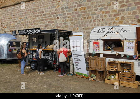 People around Montjuic castle in the city of Barcelona, for a city festival with different food trucks - Stock Photo