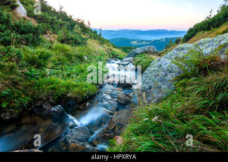 Beautiful little waterfall in mountains with white foamy silky water - Stock Photo