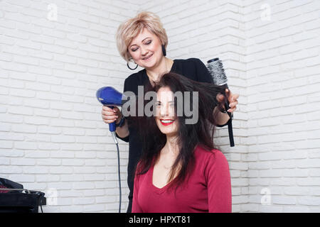 Beautiful woman at the hairdresser blow drying her hair. Drying hair with hair dryer and round brush.  Happy young - Stock Photo