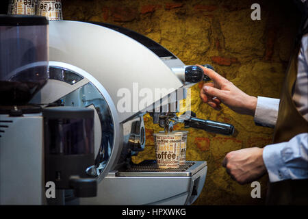 The barman prepares coffee on a professional coffee machine in vintage style. - Stock Photo
