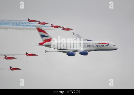 Red Arrows flying in formation with a British Airways Airbus A380 - Stock Photo