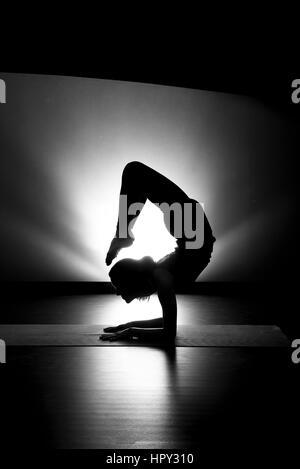 Woman doing yoga scorpion pose silhouette black and white in studio - Stock Photo