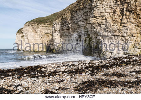 Cliffs at Thornwick Bay on Flamborough Headland, Yorkshire, England with wave crashing against the rocks. - Stock Photo