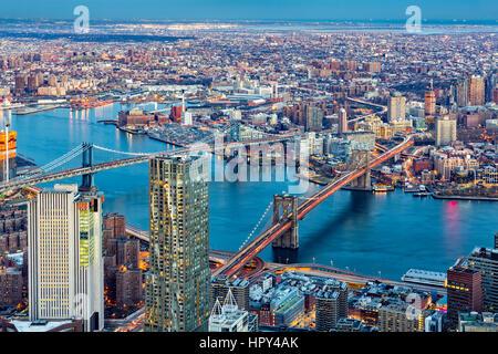 Brooklyn and Manhattan bridges span East River at dusk, between Manhattan island and Brooklyn borough - Stock Photo