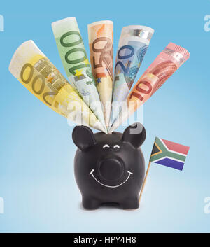 Ten,twenty,fifty,one hundred and a 200 Euro banknote in a smiling piggybank of South Africa.(series) - Stock Photo