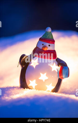 Christmas themed penguin lantern glowing in snow outdoors - Stock Photo