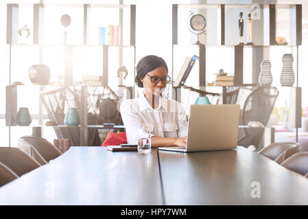 Attractive young professional well educated black woman busy typing on her notebook while seated at her dining room - Stock Photo