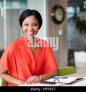 Square image of happy african woman smiling while looking into camera while wearimg a colourful orange blouse and - Stock Photo