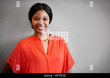 Portrait of black businesswoman smiling at camera while wearing a bright orange blouse while standing against a - Stock Photo