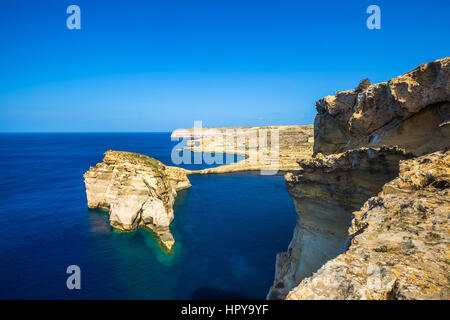 Gozo, Malta - Tha beautiful Fungus Rock on the Island of Gozo with the Azure window at background and clear blue - Stock Photo