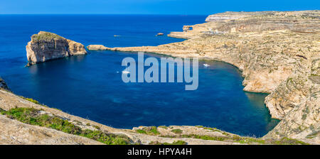 Gozo, Malta - Panoramic skyline view of Dwejra bay with Fungus Rock, Azure Window and sailboat on a nice hot summer - Stock Photo