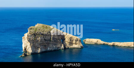 Gozo, Malta - The famous Fungus Rock on the island of Gozo on a beautiful hot summer day with crystal clear blue - Stock Photo