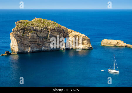 Gozo, Malta - The amazing Fungus Rock at Dwejra bay with sailboat, blue sea water and sky on a beautiful summer - Stock Photo