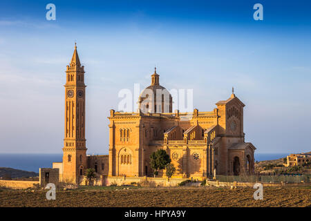 Gozo, Malta - The Basilica of the National Shrine of the Blessed Virgin of Ta' Pinu at sunset with clear blue sky - Stock Photo