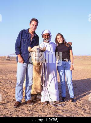 Smiling camel driver with young couple, Dubai Desert, Dubai, United Arab Emirates - Stock Photo