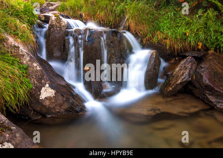 Beautiful waterfall in mountains with white foamy water - Stock Photo