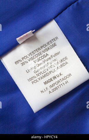 label in blue jacket made in UK 65% polyester 35% viscose lining 100% nylon - Stock Photo