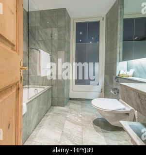 Modern minimalistic hotel bathroom with marble tiles covered walls interiors - Stock Photo