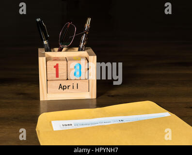 Wooden letters in calendar with Form 1040 income tax for 2016 showing tax day for filing is April 18 2017 - Stock Photo