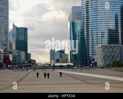 Four heavily-armed military personnel patrol the deserted esplanade at the Grande Arche at La Défense, early on - Stock Photo