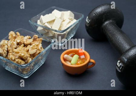 Dumbbell, walnut, tofu and dietary supplements on dark background: fitness and weight loss concept. - Stock Photo