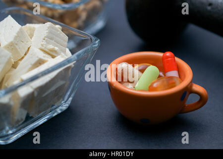 Closeup on dumbbell, walnut, tofu and dietary supplements on dark background: fitness and weight loss concept. - Stock Photo