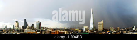 The Shard and the business district, panoramic view with dramatic sky, London, UK - Stock Photo