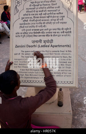 Man going over information plate with ink, Zenani Deorhi, Amer Fort, Jaipur, India - Stock Photo