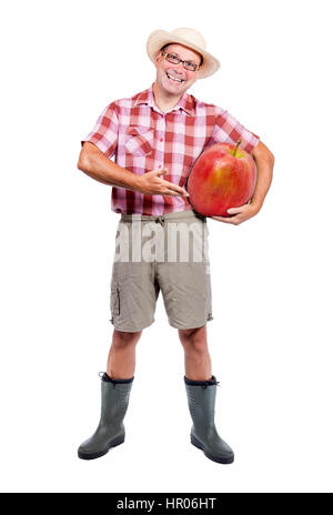 Gardener offers large red apple isolated on white background. Cheerful farmer shows harvest fruits. Funny man carries - Stock Photo