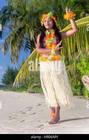 Hula Hawaii dancer dancing on the beach with palms trees. Ethnic woman in costume dancer Hawaii hula dancing in - Stock Photo