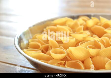 Dry conchiglie pasta shells in a stainless steel bowl - Stock Photo