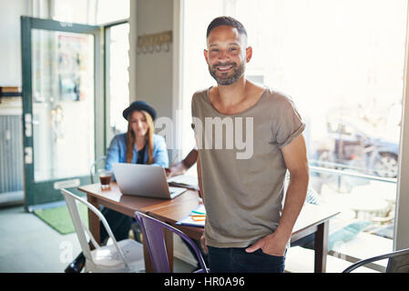 Young casual looking man with hand in pocket looking at camera on background of people at table. - Stock Photo