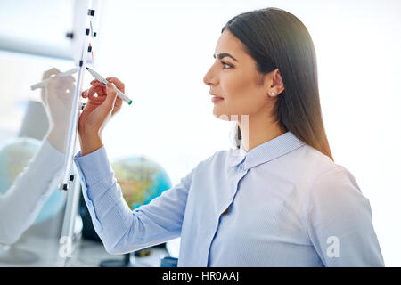 Side view on beautiful young adult woman in long brown hair and blue button collar shirt writing on board with marker - Stock Photo