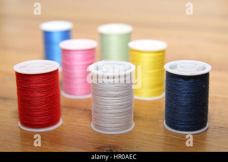 Multi-colored cotton reels or bobbins on a wooden sewing table - Stock Photo